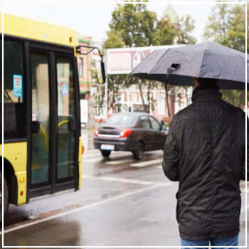 man approaching bus in the rain