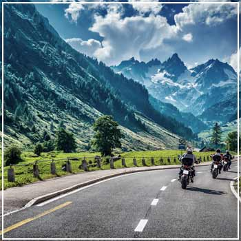 Motorcyclists riding by a mountain range