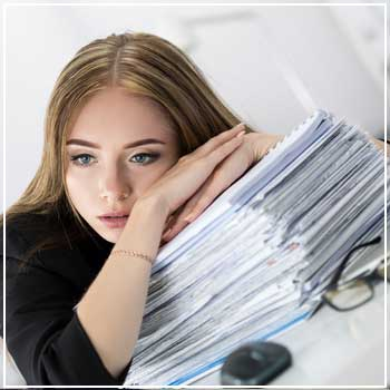Woman stressed out with a stack of paperwork
