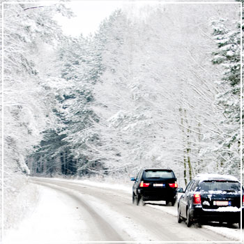 Two cars driving in snowy conditions