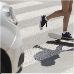 skateboarder crossing in front of car