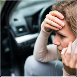 distraught woman on her phone after an accident