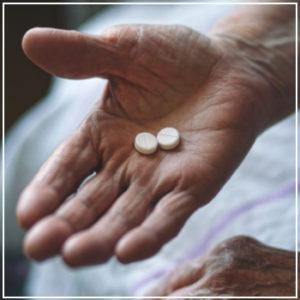 elderly hand holding pills